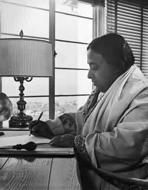 Paramahansa Yogananda writing at his desk