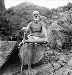 Ramana Maharshi sitting on rock during his daily walk on Arunachala mountain